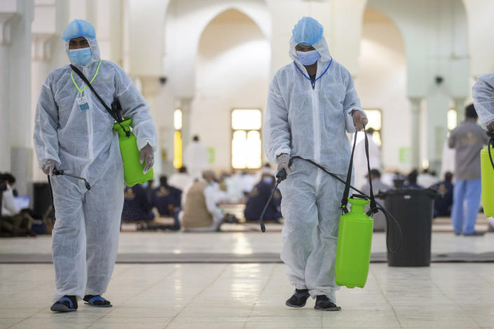 Health officials spray disinfectant inside the Namira Mosque in Arafat during the annual hajj pilgrimage near the holy city of Mecca, Saudi Arabia, Thursday, July 30, 2020. This year's hajj was dramatically scaled down from 2.5 million pilgrims to as few as 1,000 due to the coronavirus pandemic. (Saudi Ministry of Media via AP)