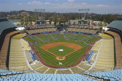 Fans line up on the field during Los Angeles Dodgers' On-Field Photo Day prior to the Dodgers' baseball game against the Colorado Rockies, Saturday, July 13, 2013 in Los Angeles. (AP Photo/Mark J. Terrill)