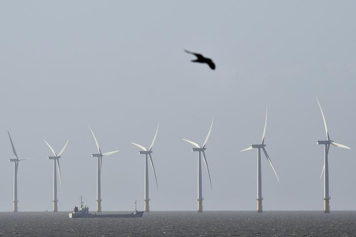 A cargo ship passes in front of an off-shore wind farm in the English Channel near Clacton-on-Sea in south east England