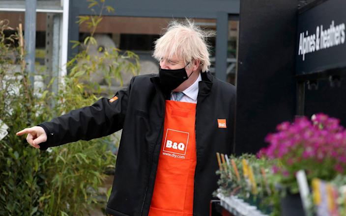 Britain's Prime Minister Boris Johnson gestures as he visits the garden centre of a DIY shop in Middlesbrough - SCOTT HEPPELL