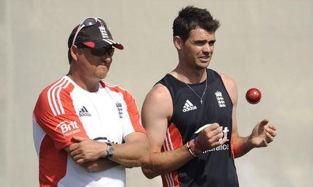 England's Anderson throws a ball up as he stands with coach Saker during a training session at the ICC Global cricket academy in Dubai