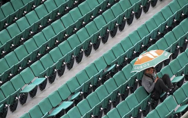 A spectator protects himself from rain during a men's singles match between Novak Djokovic of Serbia and Joao Sousa of Portugal at the French Open tennis tournament at the Roland Garros stadium in Paris May 26, 2014. REUTERS/Gonzalo Fuentes (FRANCE - Tags: SPORT TENNIS)