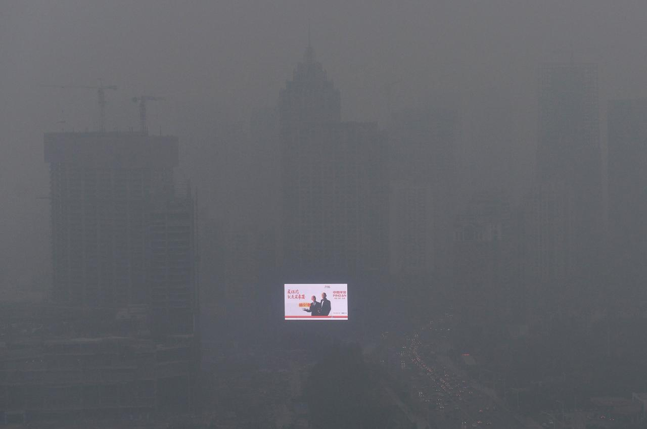 """An electronic screen is seen on a building amid heavy smog in Shenyang, Liaoning province in this October 28, 2013 file photo. China will """"declare war"""" on pollution, Premier Li Keqiang said on March 5, 2014 as the country began its annual meeting of parliament. Picture taken October 28, 2013. REUTERS/Stringer/Files (CHINA - Tags: ENVIRONMENT POLITICS HEALTH) CHINA OUT. NO COMMERCIAL OR EDITORIAL SALES IN CHINA"""
