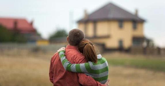 Couple hugging each other, lookinga at house in distance copyright luxorphoto/Shutterstock.com