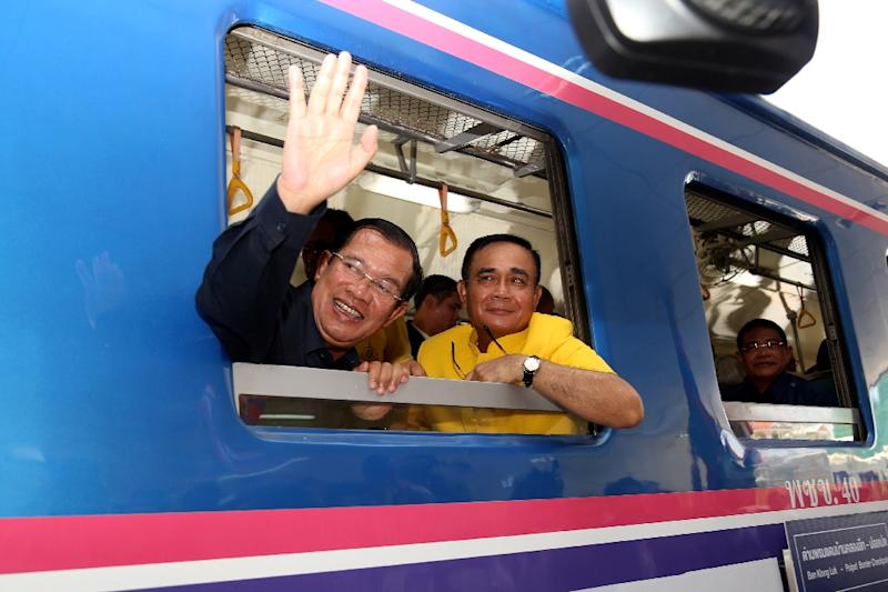 Cambodia's Prime Minister Hun Sen (left) and his Thai counterpart Prayut Chan-O-Cha aboard a train during a ceremony reconnecting a railway line between the two countries