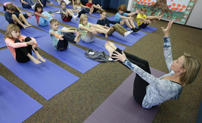 In this Dec. 11, 2012 picture, Yoga instructer Kristen McCloskey, right, leads a class of third graders at Olivenhain Pioneer Elementary School in Encinitas, Calif. Administrators of the Encinitas Union School District are treading softly as they pioneer what is believed to be the first district-wide yoga program of its kind, while trying to avoid a legal dispute over whether yoga is just exercise or an intrinsically spiritual practice. (AP Photo/Gregory Bull)