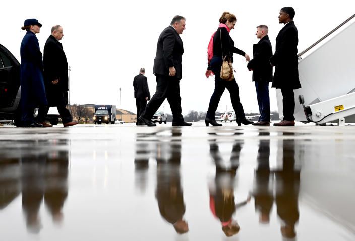 Secretary of State Mike Pompeo, center, walks with his wife Susan, to board a plane as he departs on a multi-country trip, Thursday, Feb. 13, 2020 at Andrews Air Force Base, Md. (Andrew Caballero-Reynolds/Pool via AP)