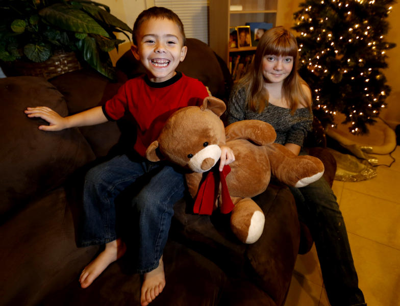 McKenna Pope, 13, right, and her brother Gavyn Boscio, 4, pose for a photo at their home in Garfield, N.J. on Thursday, Dec. 6, 2012. Pope started a petition demanding the toy company Hasbro make its Easy-Bake Oven more boy friendly. She was inspired to do so when Gavyn put the oven on his Christmas wish list and she and their mother, Erica Boscio, found the toy only available with girls on the packaging and in pink or purple colors. The petition garnered more than 30,000 signatures in a little more than a week. (AP Photo/Julio Cortez)