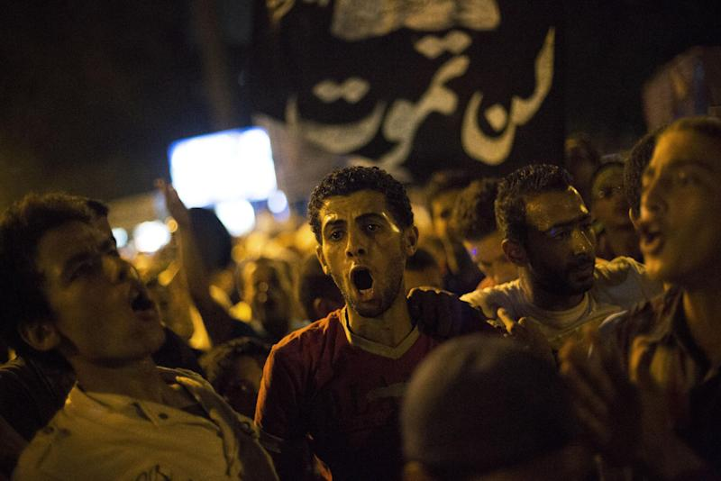 """Supporters of Egypt's ousted President Mohammed Morsi chants slogans against the Egyptian Army after """"Iftar"""" during a protest near Cairo University in Giza, Egypt, Sunday, Aug. 4, 2013. (AP Photo/Manu Brabo)"""