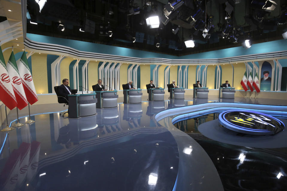 In this picture made available by Young Journalists Club, YJC, presidential candidates for June 18, from left to right, Mohsen Rezaei, Alireza Zakani, Mohsen Mehralizadeh, Amir Hossein Ghazizadeh Hashemi, Saeed Jalili, Ebrahim Raisi, , and Abdolnasser Hemmati attend their second TV debate in a state-run TV studio, in Tehran, Iran, Tuesday, June 8, 2021. Iran's seven presidential candidates on Tuesday put all the problems of the Islamic Republic squarely on the shoulders of the one man who wasn't there to defend himself: Outgoing President Hassan Rouhani. (Morteza Fakhri Nezhad/ Young Journalists Club, YJC via AP).