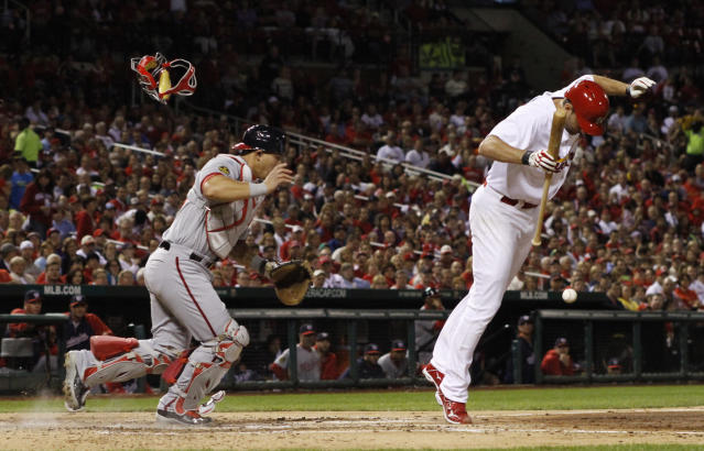 St. Louis Cardinals' Adam Wainwright dodges his own sacrifice bunt as Washington Nationals catcher Wilson Ramos tosses aside his mask to field the bunt in the fourth inning of a baseball game Monday, Sept. 23, 2013, at Busch Stadium in St. Louis. (AP Photo/St. Louis Post-Dispatch, Chris Lee)