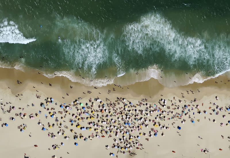 FILE PHOTO: People enjoy the sunny weather at Ipanema beach in Rio de Janeiro