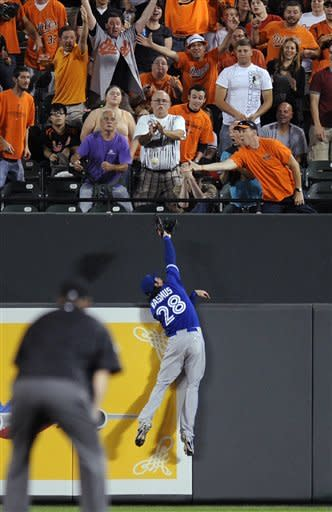 Toronto Blue Jays center fielder Colby Rasmus reaches in vain for a home run by Baltimore Orioles' Nate McLouth during the first inning of a baseball game, Wednesday, Sept. 26, 2012, in Baltimore. (AP Photo/Nick Wass)