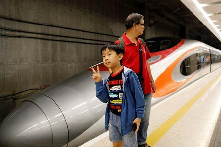 A boy poses beside a Guangzhou-Shenzhen-Hong Kong Express Rail train at West Kowloon Terminus on the first day of service of the Hong Kong Section of the Guangzhou-Shenzhen-Hong Kong Express Rail Link, in Hong Kong, China September 23, 2018. REUTERS/Tyrone Siu