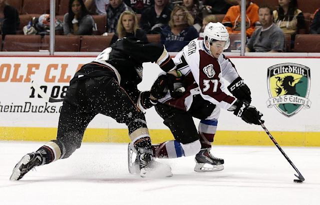 Colorado Avalanche center Colin Smith, right, shoots past Anaheim Ducks defenseman Mark Fistric during the first period of an NHL preseason hockey game in Anaheim, Calif., Sunday, Sept. 22, 2013. (AP Photo/Chris Carlson)