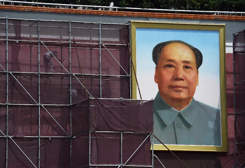 Workers pictured next to the giant portrait of late communist leader Mao Zedong in Beijing's Tiananmen Square on July 23, 2015 (AFP Photo/Greg Baker)