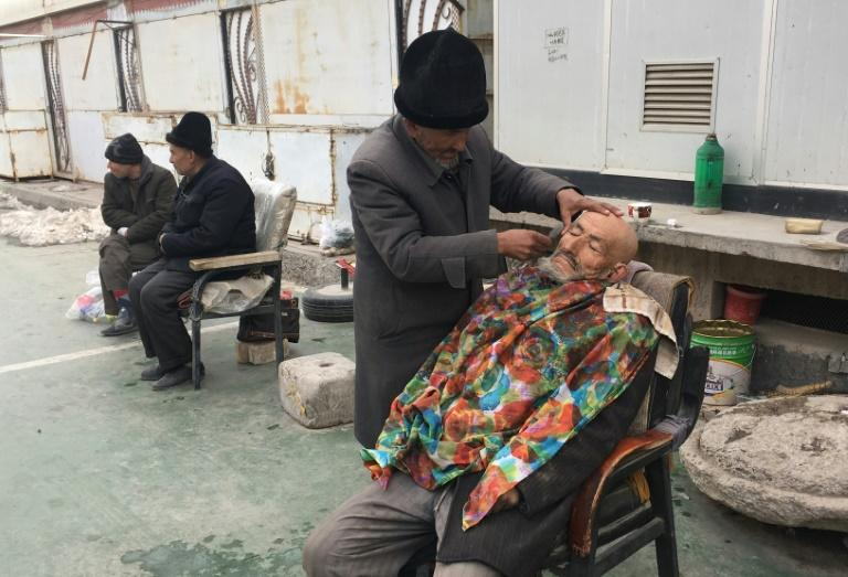 A barber shaves a man outside of a mosque in Kashgar, in China's western Xinjiang region which one of the most policed places on earth
