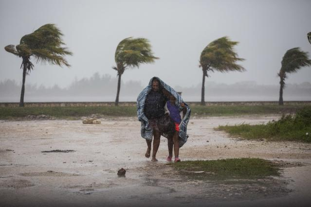<p>A woman and child use a blanket as protection from wind and rain as they walk in Caibarien, Cuba, Friday, Sept. 8, 2017. Hurricane Irma battered Cuba on Saturday with deafening winds and unremitting rain, pushing seawater inland and flooding homes before taking aim at Florida. Early Saturday, the hurricane center said the storm was centered about 10 miles (15 kilometers) northwest of the town of Caibarien. (Photo: Desmond Boylan/AP) </p>
