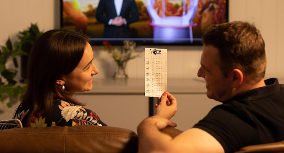 A woman holds up a lottery ticket to a man on a couch as they watch the draw.