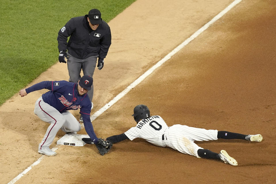 Chicago White Sox's Billy Hamilton (0) steals third on a throw from Minnesota Twins catcher Mitch Garver to third baseman Josh Donaldson as third base umpire Chris Segal watches during the fourth inning of a baseball game Wednesday, May 12, 2021, in Chicago. (AP Photo/Charles Rex Arbogast)