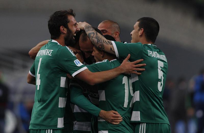 Panathinaikos' players celebrate a goal during the cup final between Athens's Panathinaikos and Thessalonikis's PAOK at the Olympic Stadium in Athens, Greece Saturday April 26, 2014. More than 300 buses carrying PAOK supporters from the northern Greek city of Thessaloniki were stopped by police at a toll station 34 kilometers (21 miles) north of the capital Athens. The supporters were searched and allowed to proceed, 20 buses at a time, to the Athens Olympic Stadium, where the Greek Cup final between soccer clubs PAOK and Panathinaikos is taking place. (AP Photo/Kostas Tsironis)