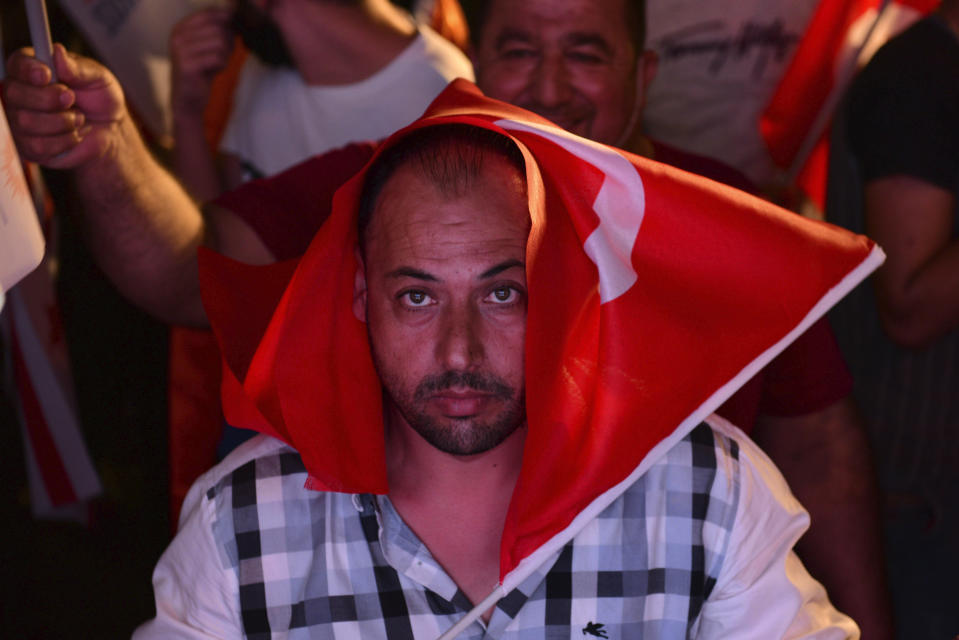 A supporter of newly elected Turkish Cypriot leader Ersin Tatar, with a Turkey flag on his head, celebrate after winning the Turkish Cypriots election, in the Turkish occupied area in the north part of the divided capital Nicosia, Cyprus, Sunday, Oct. 18, 2020. Ersin Tatar, a hardliner who favors even closer ties with Turkey and a tougher stance with rival Greek Cypriots in peace talks has defeated the leftist incumbent in the Turkish Cypriot leadership runoff. (AP Photo/Nedim Enginsoy)