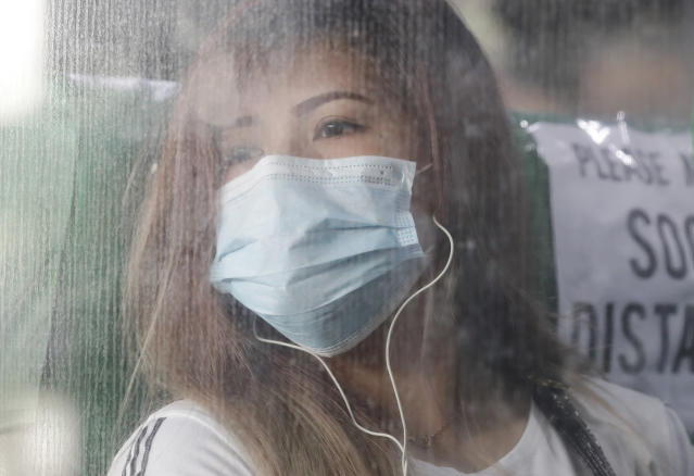 A woman wearing a protective mask looks out from a bus during the first day of a more relaxed lockdown that was placed to prevent the spread of the new coronavirus in Manila, Philippines on Monday, June 1, 2020. Traffic jams and crowds of commuters are back in the Philippine capital, which shifted to a more relaxed quarantine with limited public transport in a high-stakes gamble to slowly reopen the economy while fighting the coronavirus outbreak. (AP Photo/Aaron Favila)
