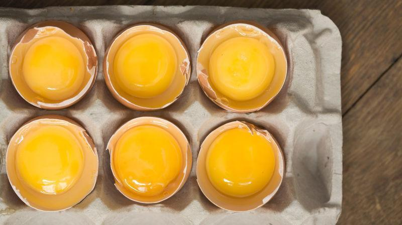 Aerial view of egg carton with each raw egg's top shell removed to show yolk inside