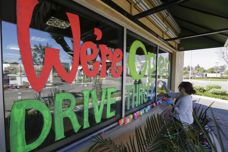 Lucy Kwak paints a sign on the window of a fast food chain's restaurant indicating that the drive-thru window is still open as well as a takeout optionduring the coronavirus outbreak in Garden Grove, Calif., Thursday, March 26, 2020. (AP Photo/Chris Carlson)