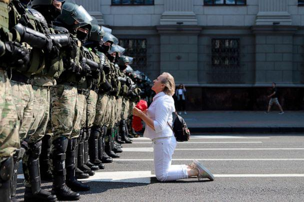 PHOTO: A woman kneels in front of a riot police line as they block Belarusian opposition supporters rally in the center of Minsk, Belarus, Aug. 30, 2020. (AP)
