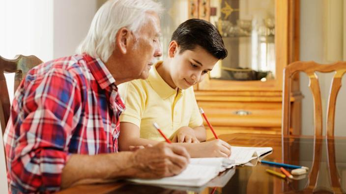 Happy little boy doing school homework with old man at home.
