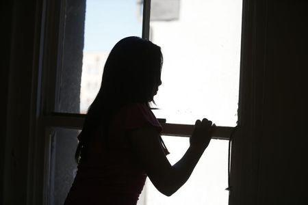 Maria, 18, who is an undocumented migrant from Central America, looks out of a window in Los Angeles, California, July 22, 2014. REUTERS/Lucy Nicholson