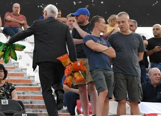Chelsea chairman Bruce Buck hands out packets of crisps to travelling Blues fans