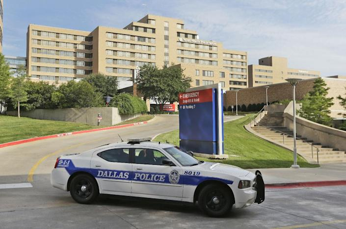 A police car drives past the entrance to the Texas Health Presbyterian Hospital in Dallas. (AP Photo/LM Otero)