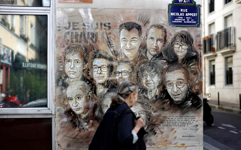 A woman walks past a mural commemorating the victims of the 2015 attack on the Charlie Hebdo offices in which 12 were killed - THOMAS COEX/AFP