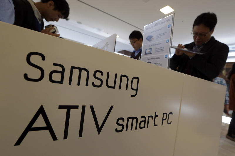 Media persons look at Samsung Electronics Co.'s ATIV smart PC which is powered by a new version of Microsoft's Windows operating system, before a media briefing in Seoul, South Korea, Wednesday, Oct. 24, 2012. Samsung Electronics said Wednesday it expects 10 percent growth in PC sales by volume this year as it bets on new PCs that are hybrids of laptops and tablets to lift sluggish PC demand. (AP Photo/Lee Jin-man)