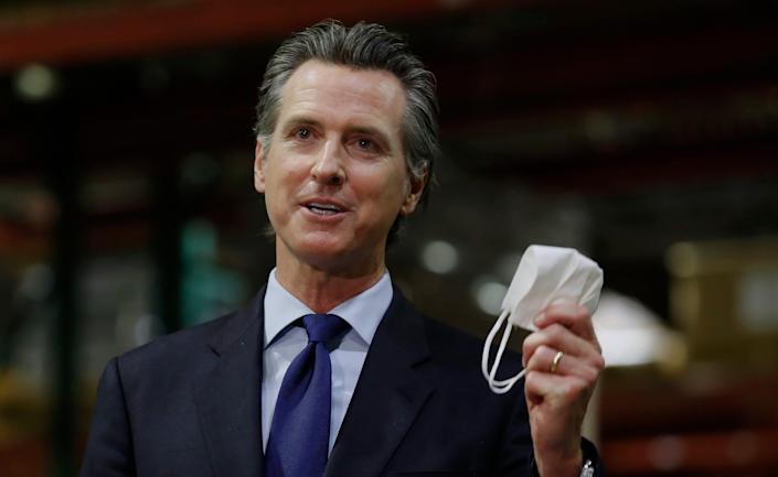 Gov. Gavin Newsom displays a face mask as he urges people to wear them to fight the spread of the coronavirus during a June 26, 2020, news conference in Rancho Cordova, Calif.