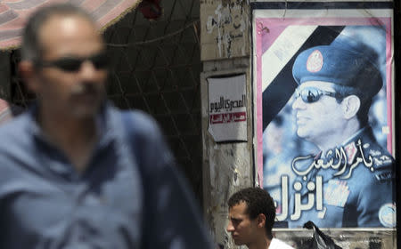 People walk in front of an election campaign poster of presidential candidate and Egypt's former army chief Sisi, along a highway in downtown Cairo
