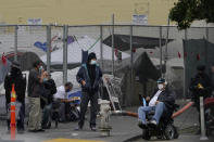 People linger on a street corner in front of tents set up in a fenced lot in San Francisco, Saturday, Nov. 21, 2020. Some counties in California are pushing ahead with plans to wind down a program that's housed homeless people in hotel rooms amid the pandemic, despite an emergency cash infusion from the state aimed at preventing those same residents from returning to the streets in cold, rainy weather as the virus surges. (AP Photo/Jeff Chiu)