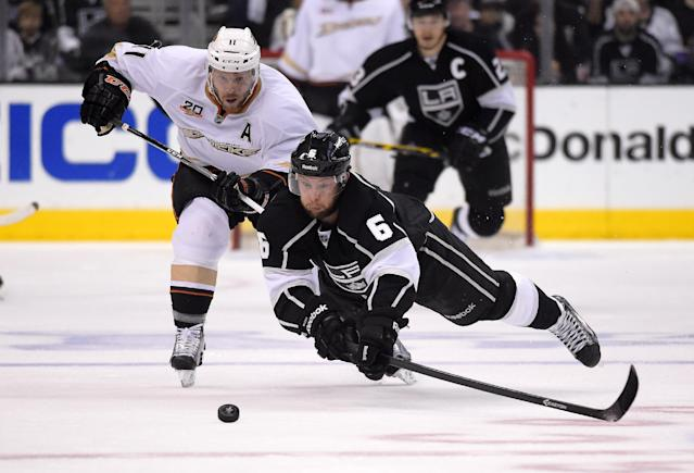 Los Angeles Kings defenseman Jake Muzzin, right, dives for the puck as Anaheim Ducks center Saku Koivu, of Finland, puts pressure on him during the first period in Game 4 of an NHL hockey second-round Stanley Cup playoff series, Saturday, May 10, 2014, in Los Angeles. (AP Photo/Mark J. Terrill)