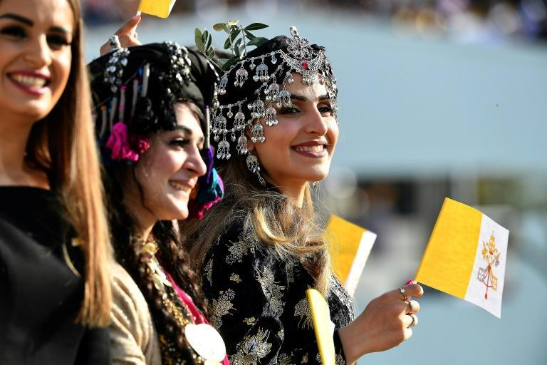 Young women dressed in traditional Kurdish clothing wave flags of the Holy See as they wait for the arrival of Pope Francis at the Franso Hariri Stadium in Arbil