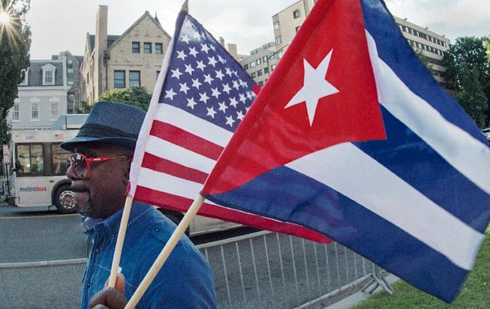 A man waves the US and Cuban flags as he walks in front of the new Cuban Embassy shortly before it's official ceremonial opening July 20, 2015, in Washington, DC (AFP Photo/Paul J. Richards)