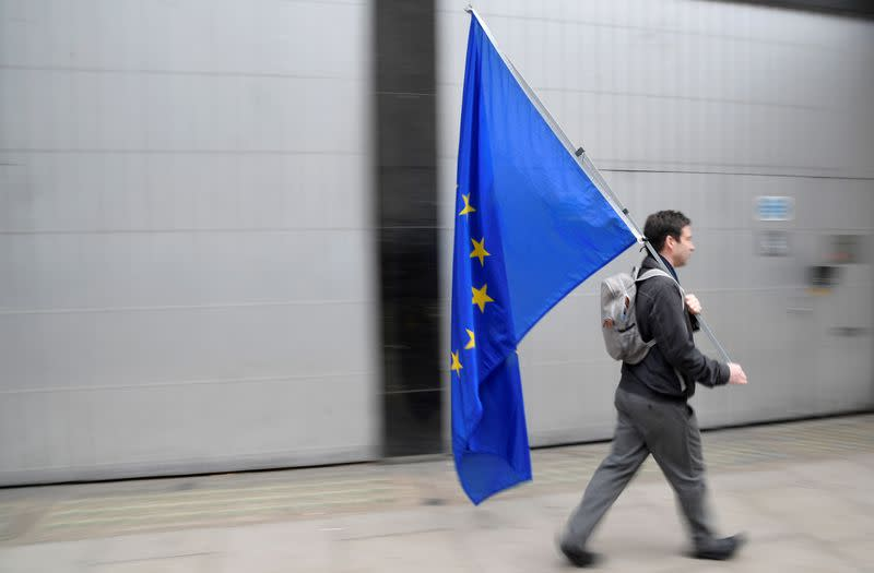 A man carries a European Union flag near the London School of Economics in London