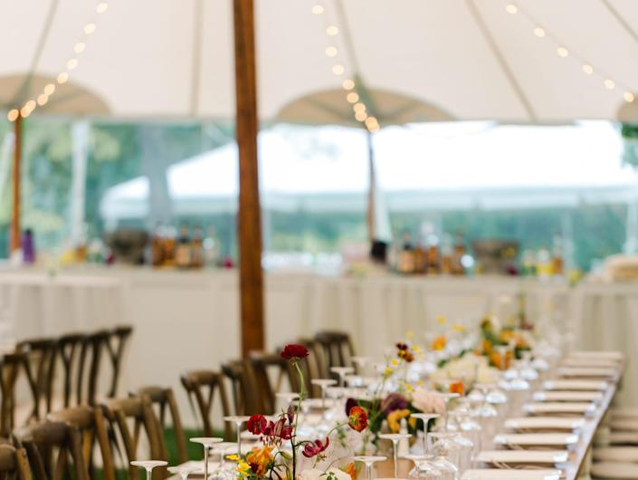 A long table set for dinner in an outdoor tent at a wedding.