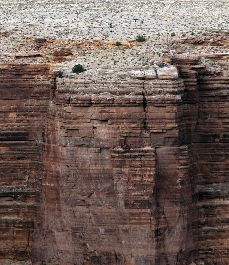 Daredevil Nik Wallenda crosses a tightrope 1,500 feet above the Little Colorado River Gorge Sunday, June 23, 2013, on the Navajo reservation outside the boundaries of Grand Canyon National Park. (AP Photo/Rick Bowmer)