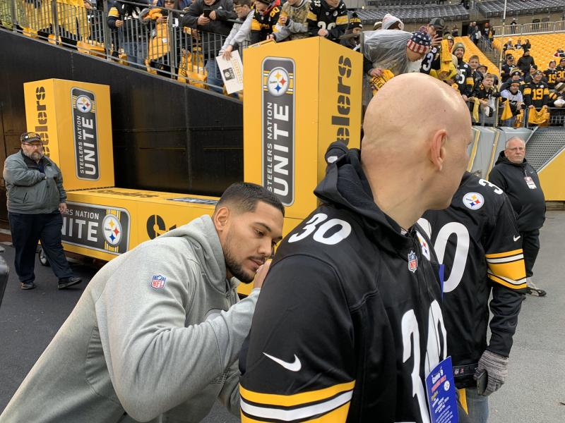 Steelers running back and cancer survivor James Conner, left, signs the jersey of a fan fighting cancer. (Brooke Pryor/Twitter)