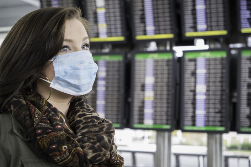 An attractive female wears a mask at the airport, possibly fearful of coronavirus.