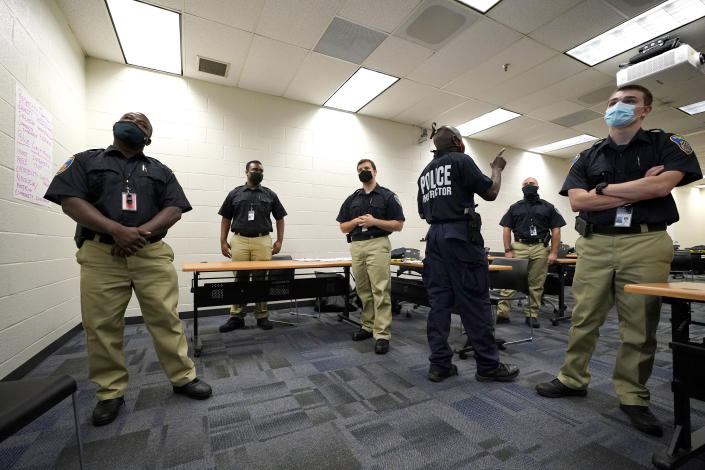 In this Sept. 9, 2020, photo Officer Edward Gillespie, third from right, leads a class in procedural justice with Baltimore Police Academy cadets in Baltimore. (AP Photo/Julio Cortez)