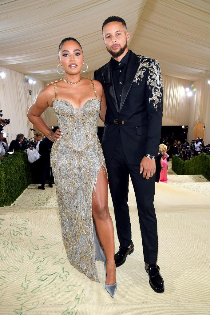 Stephen Curry wears a dark suit with a glittery pattern on the shoulder and Ayesha Curry wears a floor length thin strap glittery gown with a slit up her thigh
