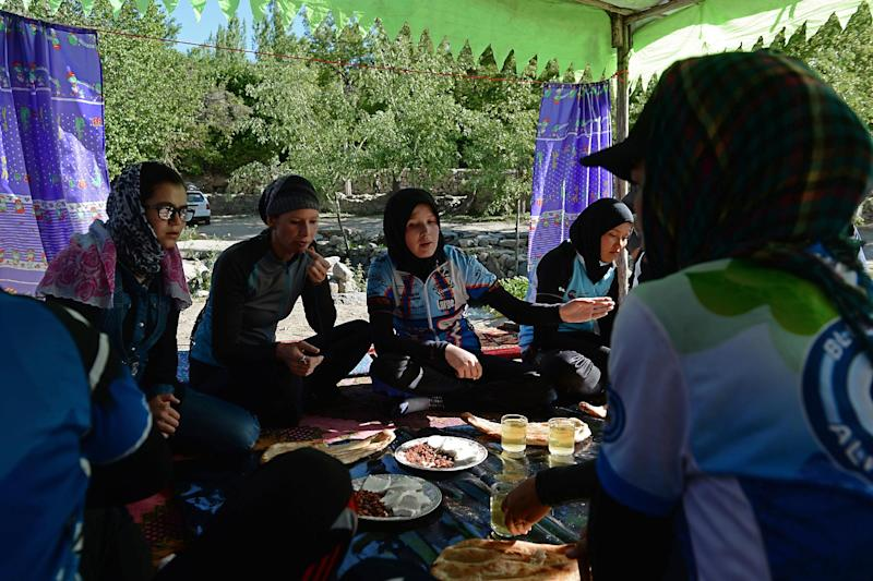Members of the Afghan national women's cycling team have breakfast following their training in Paghman district of Kabul province, June 9, 2014 (AFP Photo/Shah Marai)